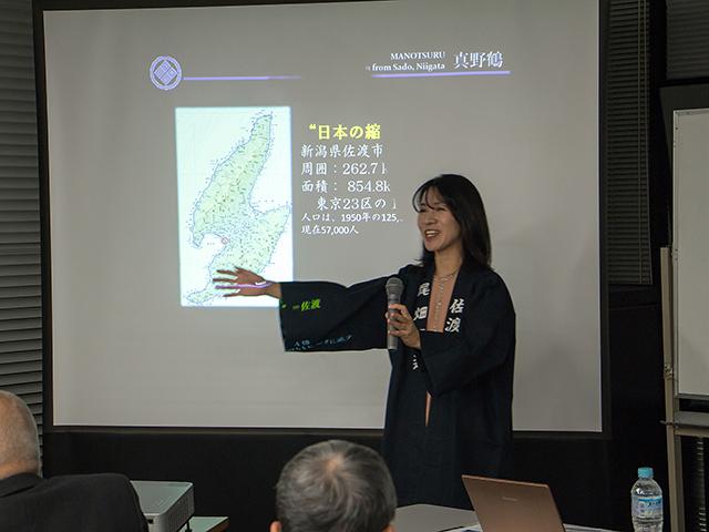 スライドを使って「学校蔵」の説明や佐渡島の魅力を紹介する尾畑さん