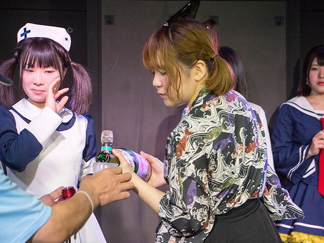 勝ち残った観客に日本酒を注ぐえりかさん