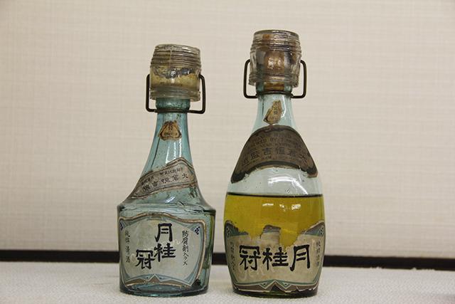 「防腐剤入ラズ」とラベルに表示された瓶詰め酒の商品化。明治期から大正期の駅売り酒コップ付き小(画像提供:月桂冠)